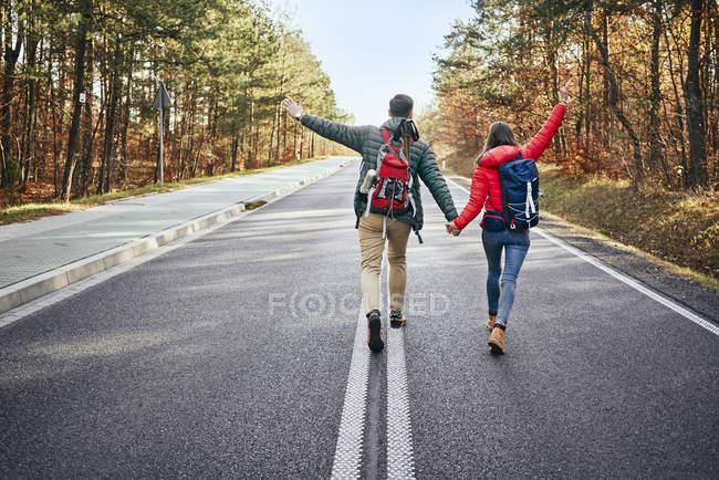 Счастливая пара, идущая посреди пустой дороги в хорошем настроении — стоковое фото