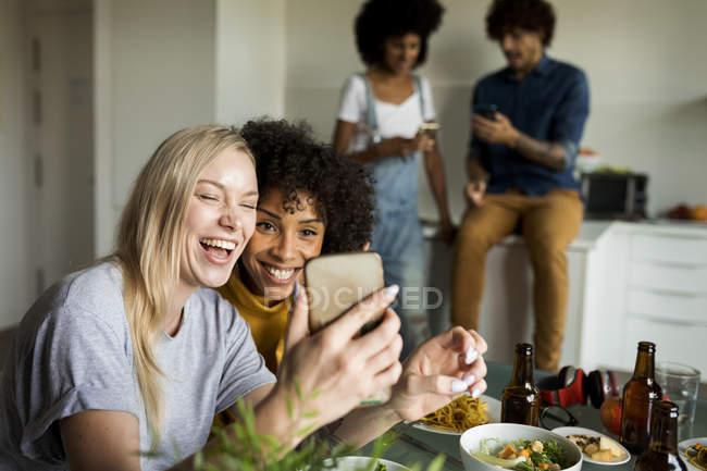 Joyeuses amies avec téléphone cellulaire assises à la table à manger — Photo de stock