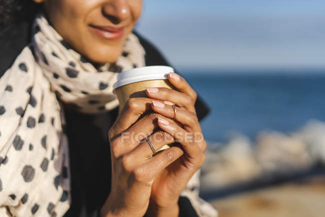 Woman's hands holding coffee to go, close-up — Stock Photo