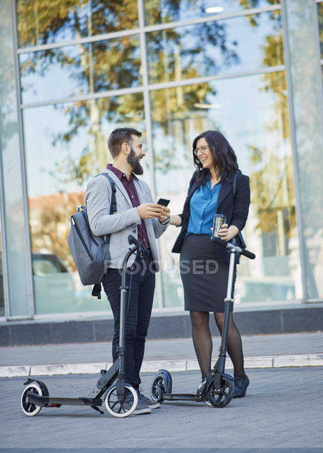Happy businessman and businesswoman with scooters talking on pavement — Stock Photo