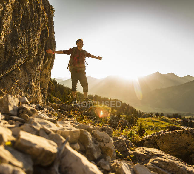 Hiking man standing in mountains, cheering — Stock Photo