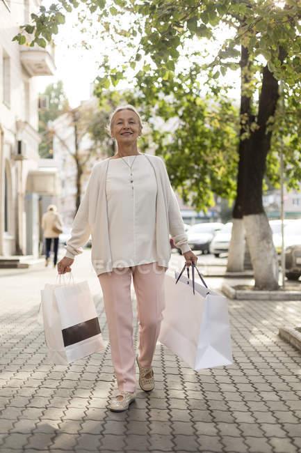 Улыбающаяся пожилая женщина идет по тротуару с пакетами для покупок — стоковое фото