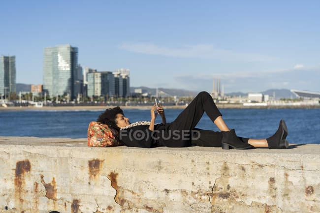 Spanien, Barcelona, schwarz gekleidete Frau, die mit dem Smartphone auf einer Mauer vor dem Meer liegt — Stockfoto