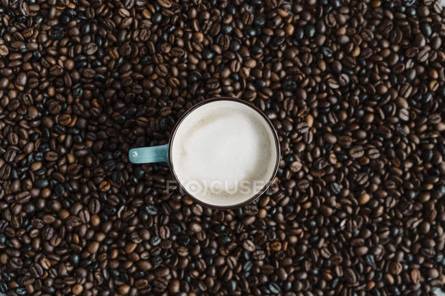Cup of white coffee between coffee beans — стокове фото