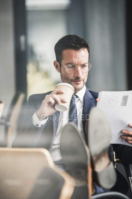 Homme d'affaires lisant des documents pendant son café braek — Photo de stock