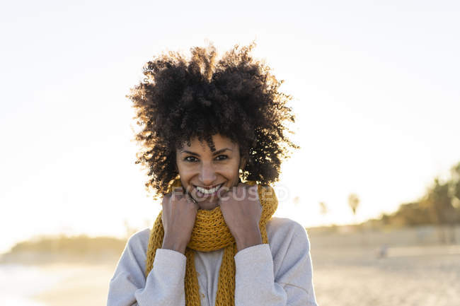 Portrait of a happy woman in the beach, wearing a yellow scarf — Stock Photo