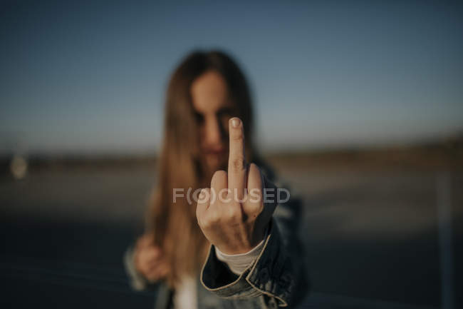 Close-up of young woman outdoors giving the finger — Stock Photo