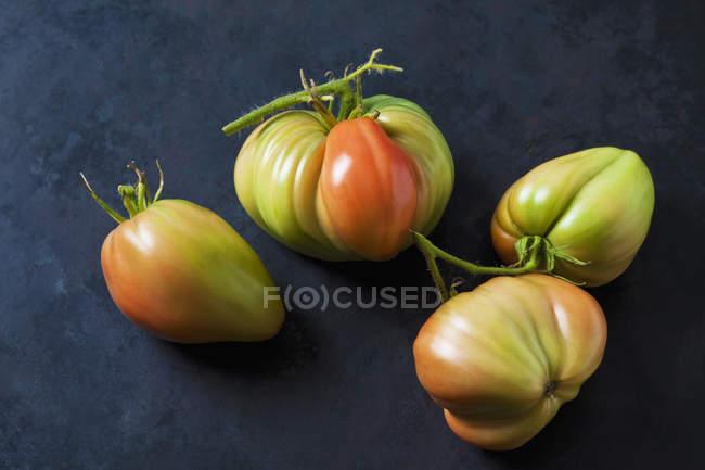 Vier Oxheart Tomaten auf dunklem Boden — Stockfoto