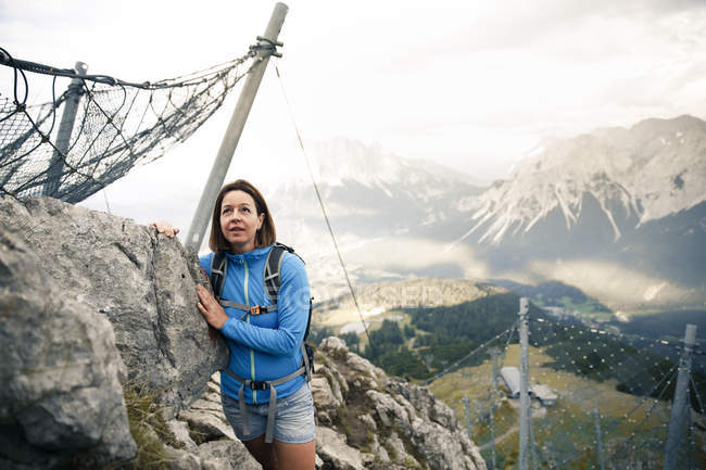 Austria, Tyrol, woman on a hiking trip in the mountains standing at rock — Stock Photo