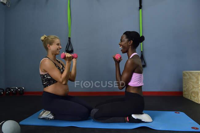Две счастливые женщины занимаются фитнесом с гантелями в спортзале — стоковое фото