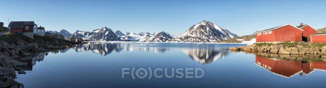 Groenlandia, Sermersooq, Kulusuk, Alpi Schweizerland, montagne e capanne di legno sulla riva che si riflettono nell'acqua — Foto stock