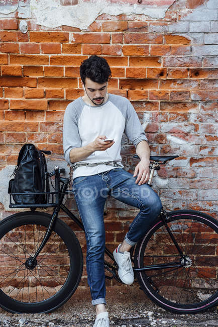 Young man with commuter fixie bike standing at brick wall with cell phone and earphones — Stock Photo
