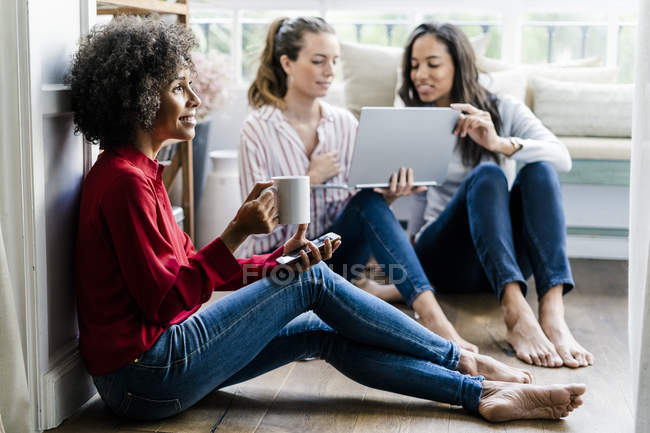 Three women with cell phone, coffee cup and laptop sitting on the floor at home — Stock Photo