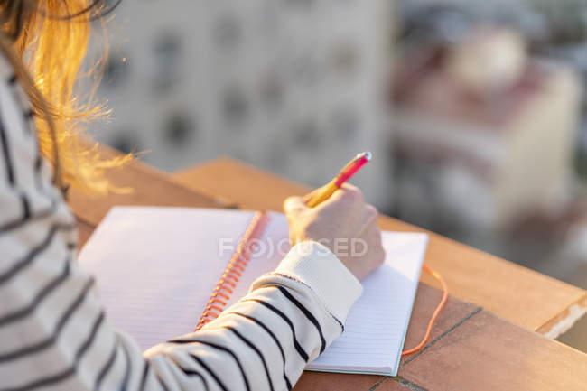 Молода жінка робить записи на терасі даху на заході сонця з частковим видом. — стокове фото