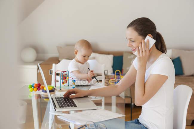 Усміхнена мати за допомогою ноутбука і мобільного телефону з маленькою донькою, що бавиться за столом удома. — стокове фото