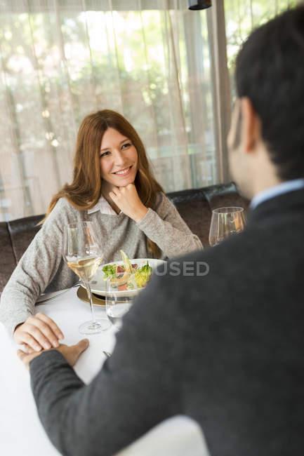 Усміхнена Жінка тримає руки з чоловіком в ресторані — стокове фото