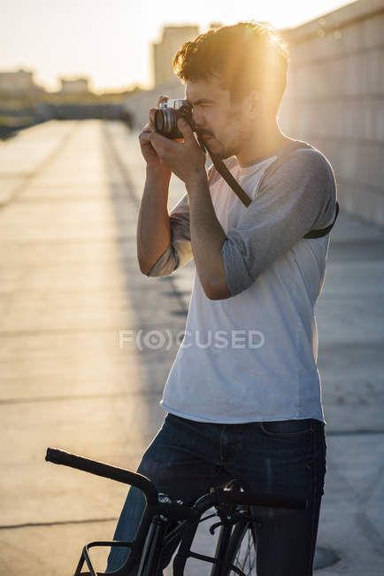Young man with commuter fixie bike taking a picture at sunset — Stock Photo
