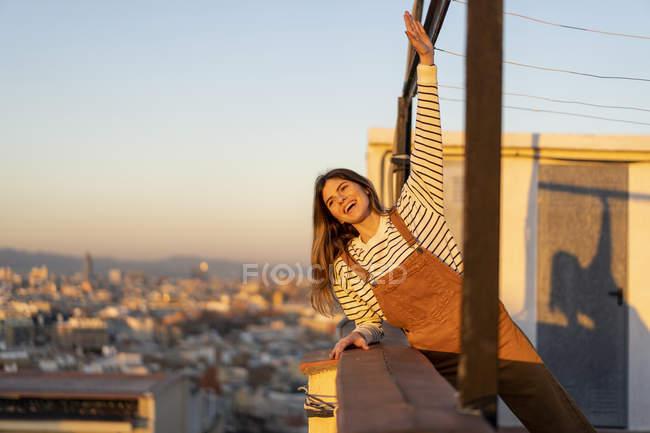 Портрет смеющейся молодой женщины, отдыхающей на террасе на крыше на закате — стоковое фото