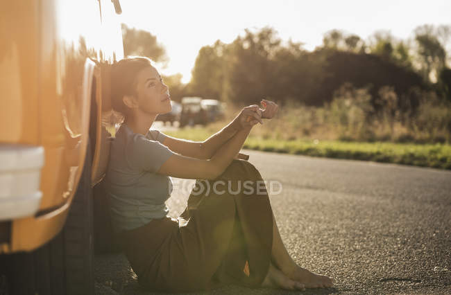 Pretty woman on a road trip with her camper, relaxing at the roadside — Stock Photo