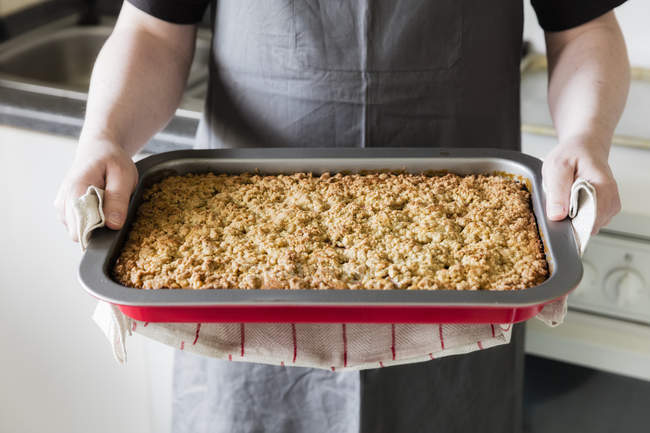 Man in kitchen holding baking tray with homemade rhubarb cake, partial view — Stock Photo