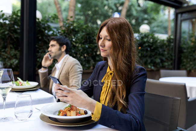 Man and woman using cell phones in a restaurant — Stock Photo