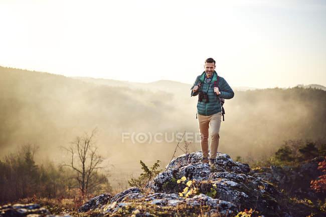 Homme en randonnée dans les montagnes marchant sur des rochers — Photo de stock