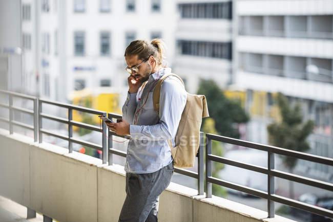 Молодий бізнесмен з рюкзаком стоячи в гаражі, використовуючи смартфон — стокове фото