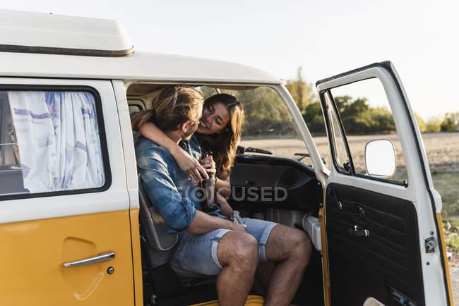 Счастливая пара, сидящая в своем трейлере, обнимающая, пьющая напиток — стоковое фото