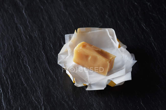 Cream toffee on wrapping paper — стоковое фото