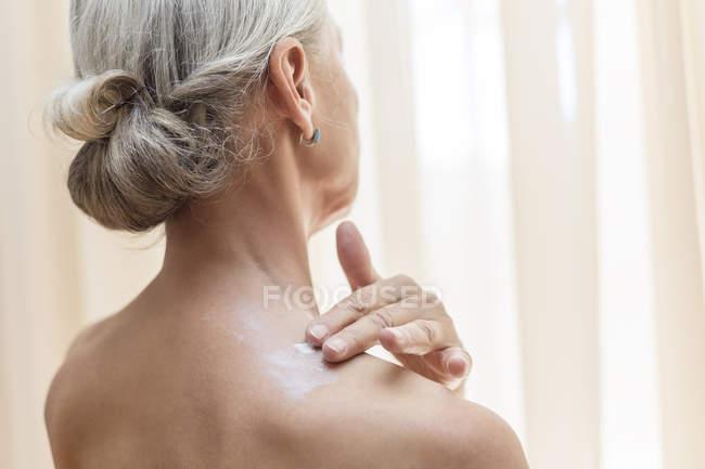 Vista posterior de la mujer mayor aplicando crema en el cuello - foto de stock