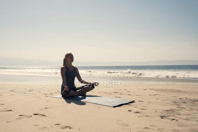 Giovane donna che esercita yoga in spiaggia — Foto stock