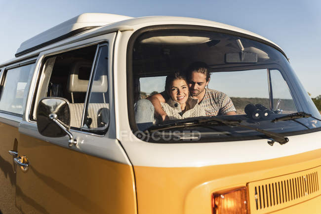 Affectionate couple sitting in their camper with arms around, watching sunset — Stock Photo