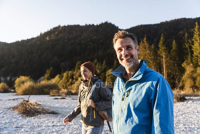 Mature couple hiking at riverside in the evening light — Stock Photo
