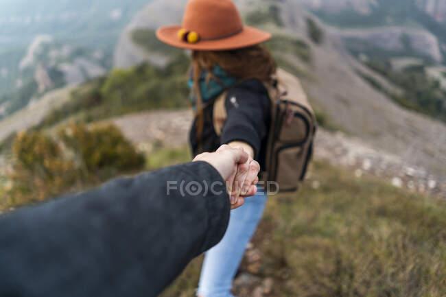 Mujer con sombrero, de pie en la montaña, sosteniendo la mano del hombre - foto de stock