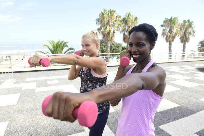 Two smiling women doing fitness exercises with dumbbells outdoors — Stock Photo