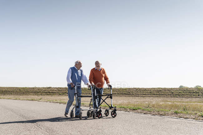 Two old friends walking on a country road, using wheeled walkers — Stock Photo