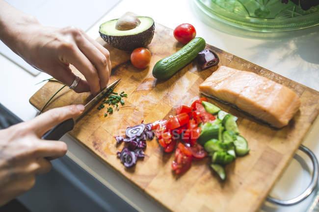 Femme préparant légumes et saumon sur planche à découper — Photo de stock
