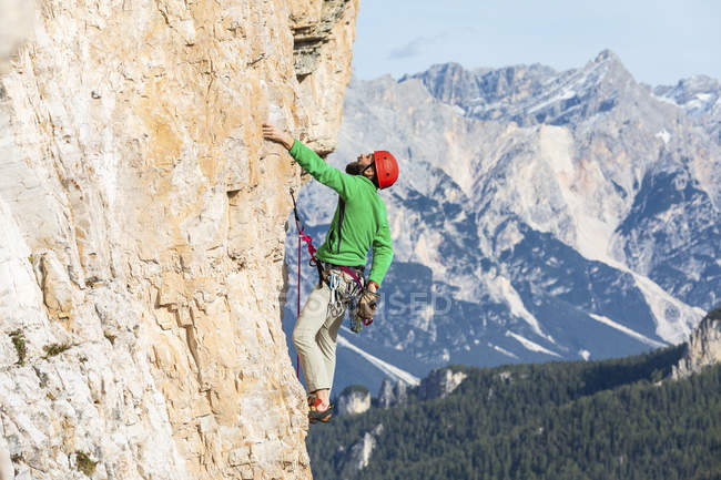 Italy, Cortina d'Ampezzo, man using chalk powder while climbing in the Dolomites mountains — стоковое фото