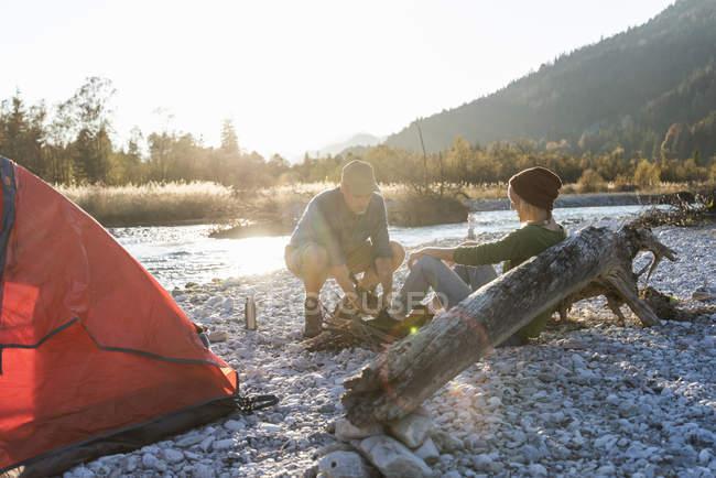 Coppia matura campeggio a riva del fiume, la raccolta di legna per un fuoco da campo — Foto stock
