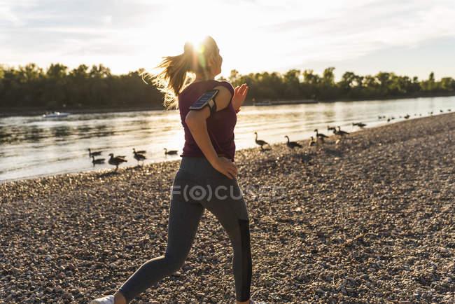 Jeune femme jogging à la rivière — Photo de stock