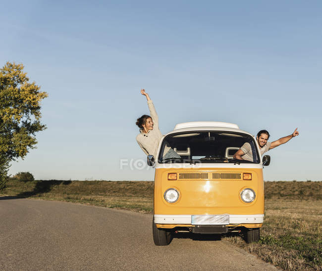 Happy couple waving and cheering out of their camper, having fun on their road trip — стокове фото
