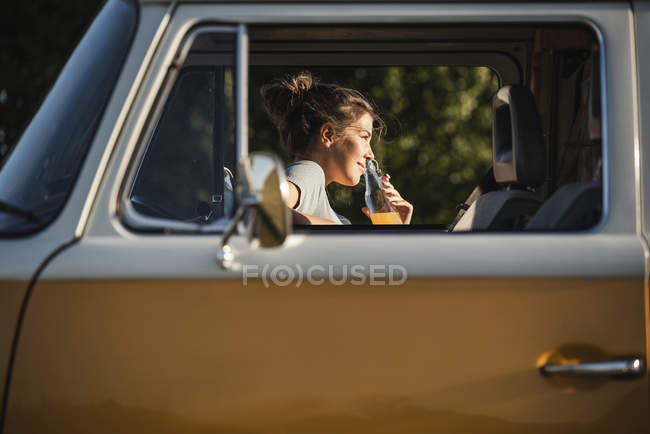 Pretty woman on a road trip with her camper, taking a break, drinking juice — Stock Photo
