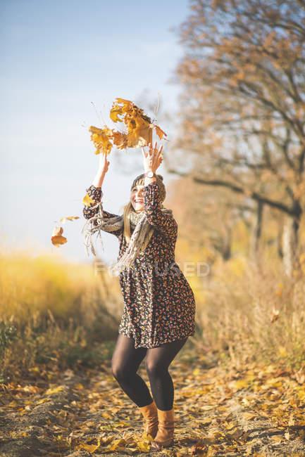 Щаслива вагітна жінка стоїть на лісовій стежці, граючи з осіннім листям. — стокове фото