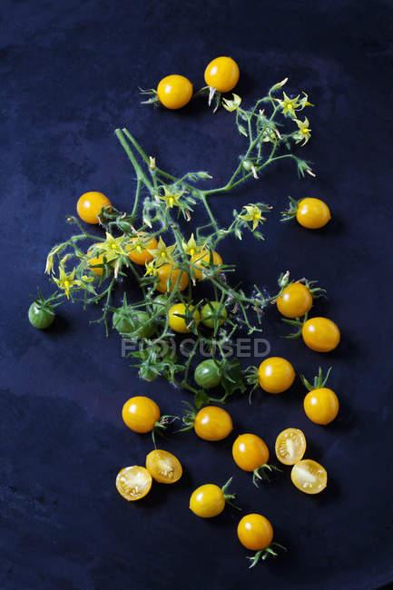 Whiole und in Scheiben geschnittene Tomaten 'Blondk?pfchen' auf dunklem Boden — Stockfoto