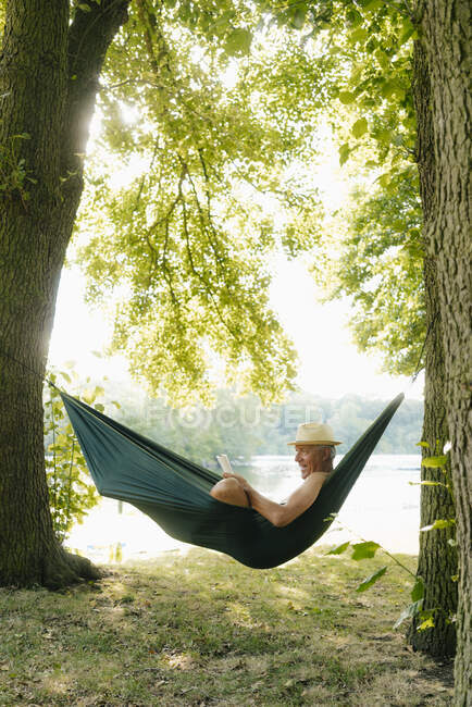 Senior man wearing straw hat relaxing in hammock at lakeshore reading book — Stock Photo