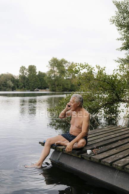 Пенсионер, сидящий на пристани у озера, разговаривает по мобильному телефону — стоковое фото
