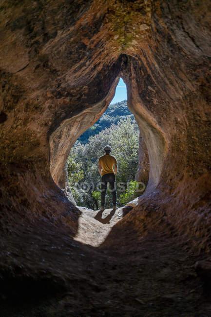Молодий чоловік стоїть у печерному вході, Кова - Сіманья (Барселона, Іспанія). — стокове фото