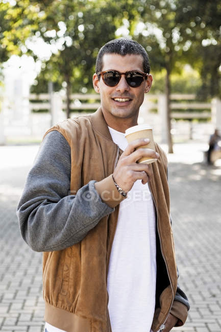 Portrait of fashionable young man wearing sunglasses and holding takeaway coffee — Stock Photo
