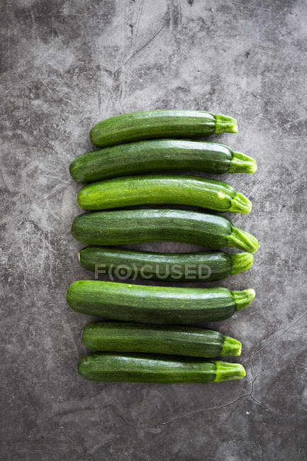 Courgettes in a row, grey background — Stock Photo