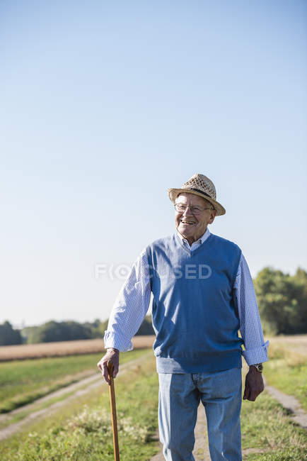 Senior man with a walking stick, walking in the fields — Stock Photo